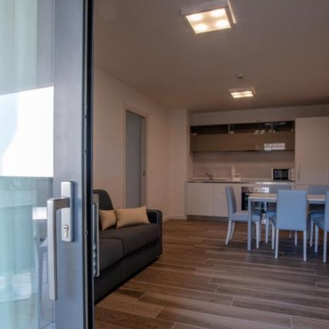 Aparthotel con cucina laccata, soggiorno componibile e divano letto.