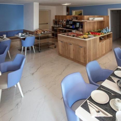 Aparthotel sala colazioni. Tavolini in laminato bianco. Mobile buffet in rovere.