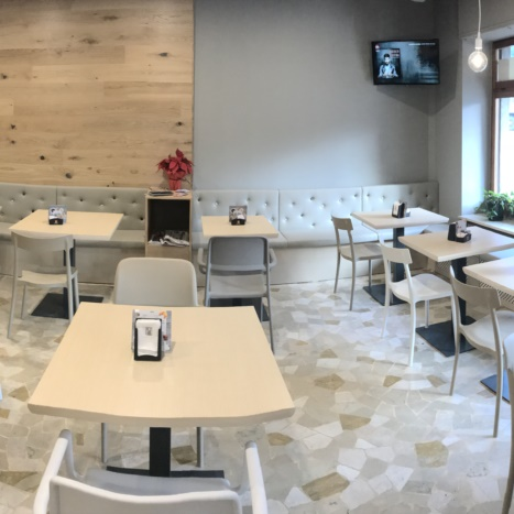 Sala con parete in rovere, tavolini in frassino e sedie in polipropilene