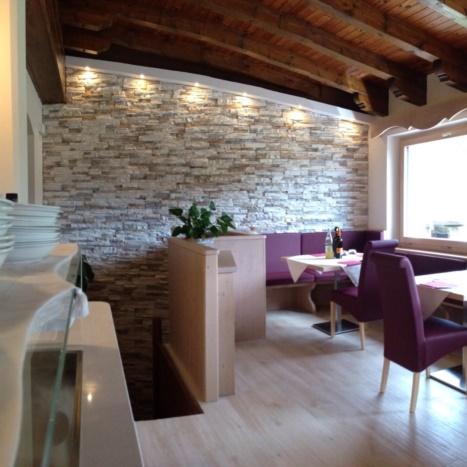 Sala da pranzo con parete in Geopietra e piastrelle effetto legno.